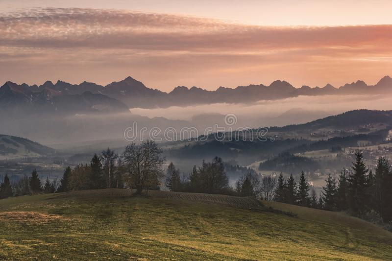 Poland, autumn, beautiful sunset over the Tatras, mountains: View. A beautiful sunset over the mountains in poland. Visible fog and city royalty free stock photo