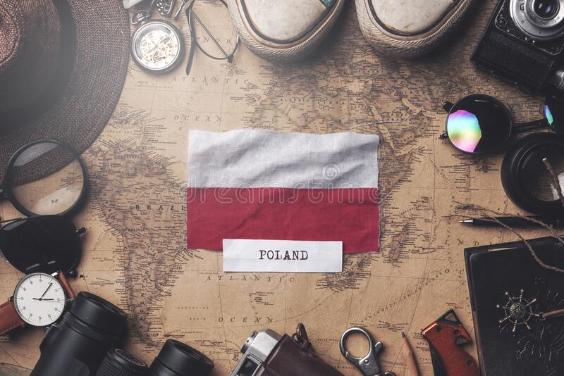 Poland Flag Between Traveler`s Accessories on Old Vintage Map. Overhead Shot.  royalty free stock photography