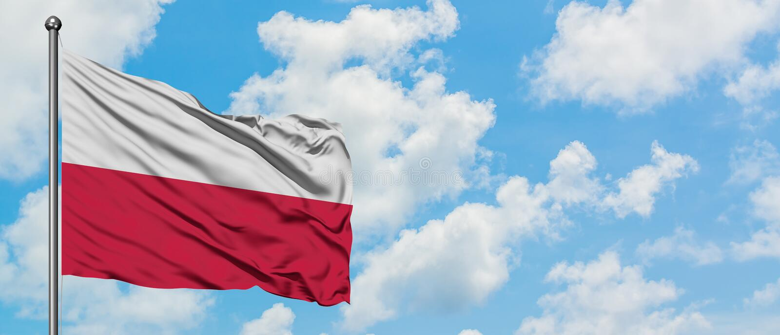 Poland flag waving in the wind against white cloudy blue sky. Diplomacy concept, international relations.  royalty free stock photography