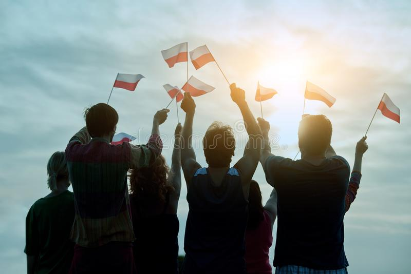 Poland patriotic people with small flags, back view. Blue morning sky background royalty free stock photography
