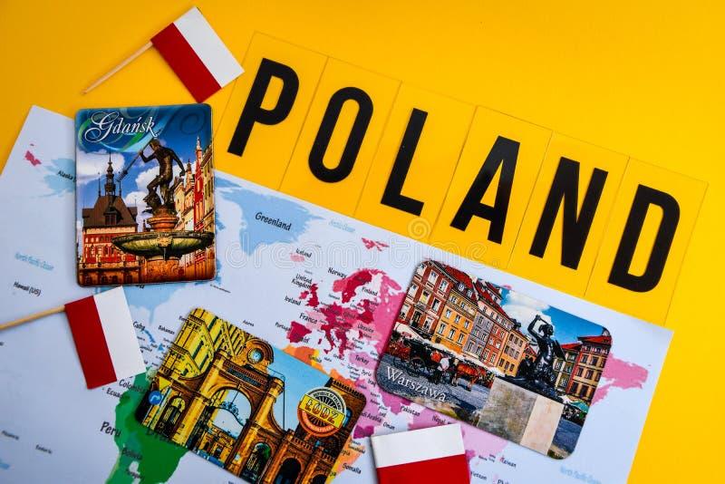 Poland travel destination, polish flag, magnets from Warsaw, Gdansk Lodz, world map. Travel concept, EU stock photography