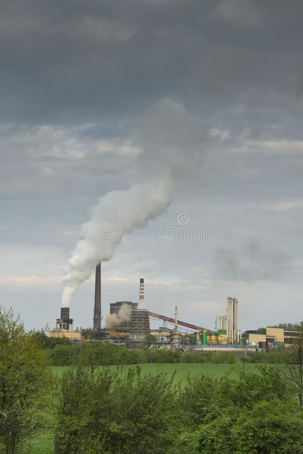 Poland, Zabrze, Biskupice Coking Plant. Seen over green field, spring royalty free stock image
