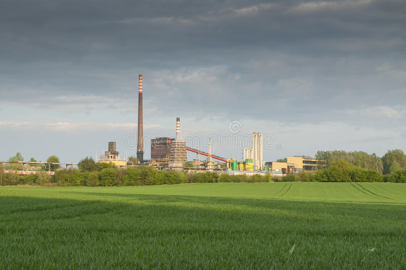 Poland, Zabrze, Biskupice Coking Plant. Seen over green field, spring royalty free stock photography