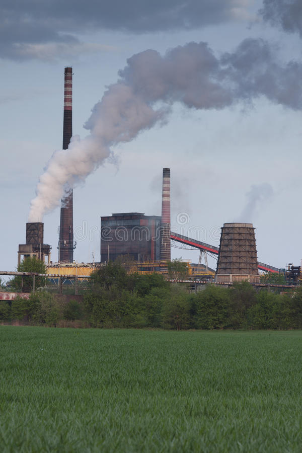 Poland, Zabrze, Biskupice Coking Plant. Seen over green field, spring stock photography