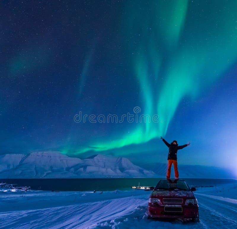 The polar arctic man Northern lights aurora borealis sky star in Norway Svalbard in Longyearbyen city moon mountains. The polar arctic man Northern lights aurora royalty free stock image