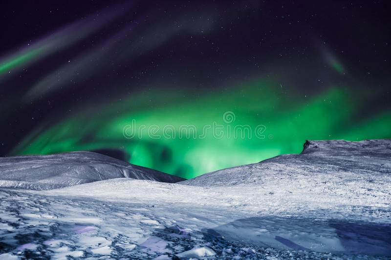 The polar arctic Northern lights aurora borealis sky star in Norway Svalbard in Longyearbyen city moon mountains stock images