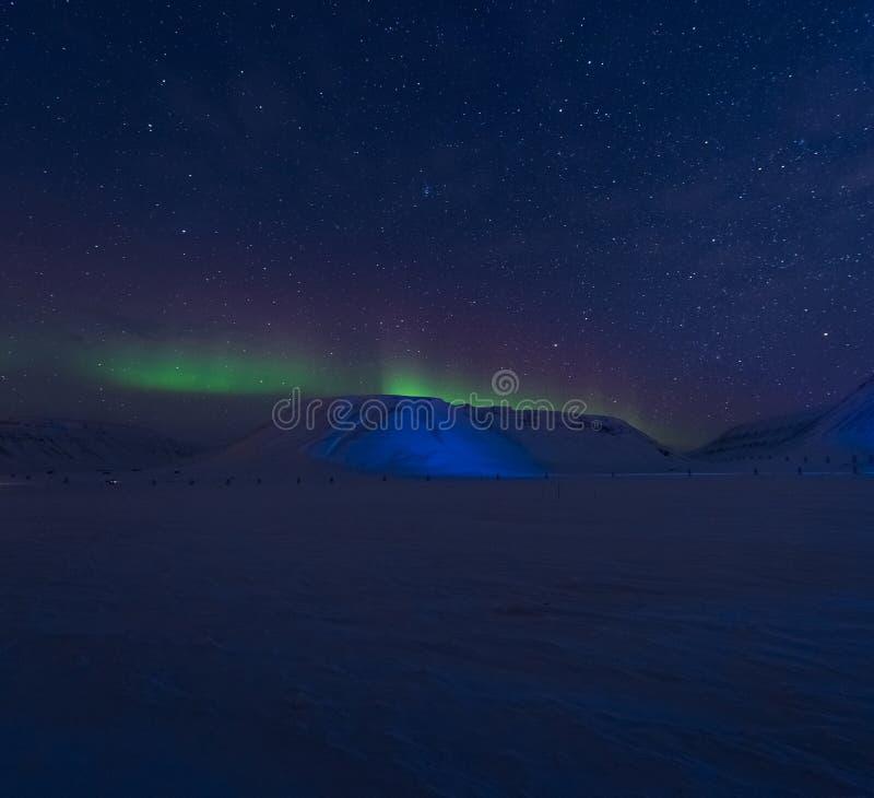 The polar arctic Northern lights aurora borealis sky star Norway Svalbard in Longyearbyen city mountains stock photography