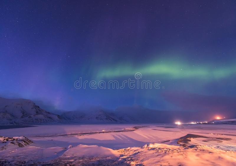 The polar arctic Northern lights aurora borealis sky star in Norway Svalbard Longyearbyen city mountains stock image
