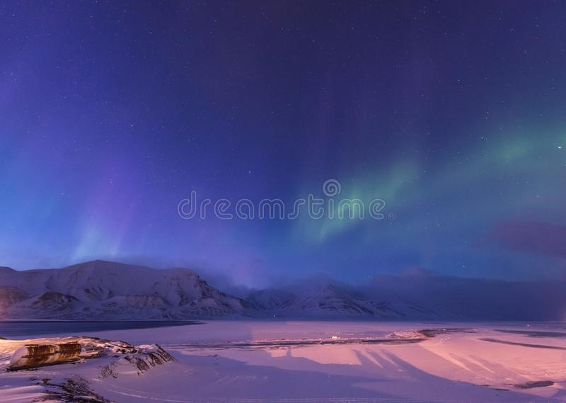 The polar arctic Northern lights aurora borealis sky star in Norway Svalbard Longyearbyen city mountains stock images