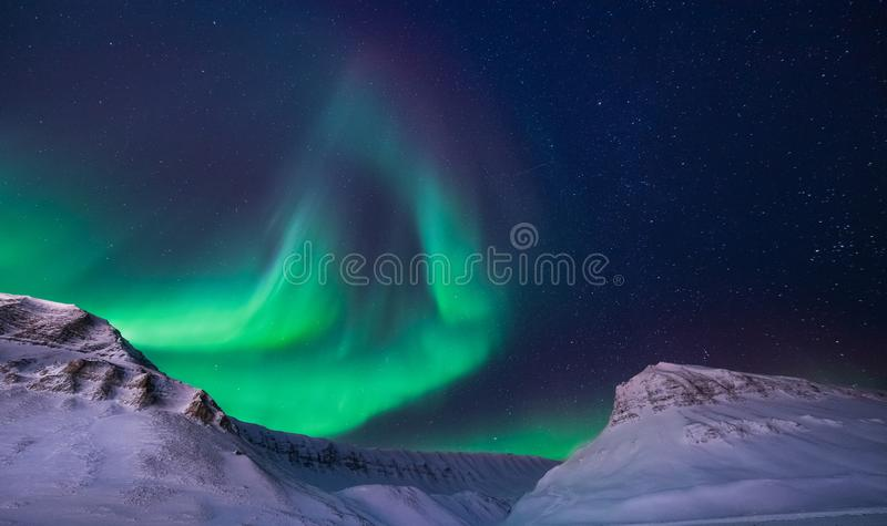 The polar arctic Northern lights aurora borealis sky star in Norway Svalbard Longyearbyen city snowscooter mountains stock images