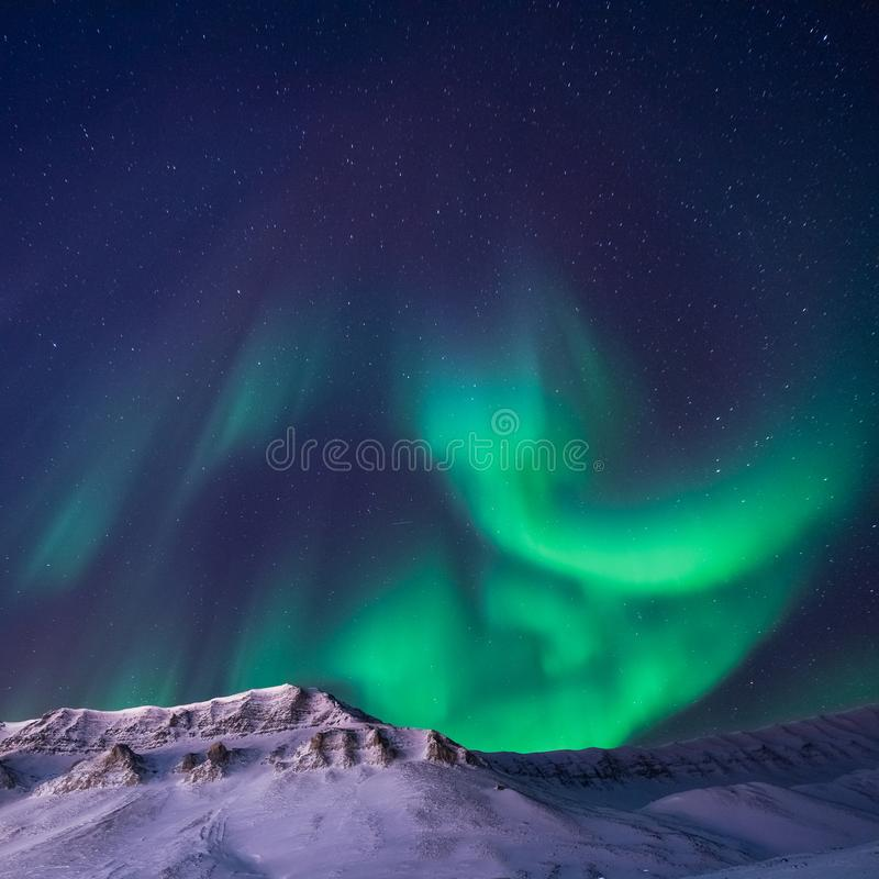 The polar arctic Northern lights aurora borealis sky star in Norway Svalbard Longyearbyen city snowscooter mountains stock image