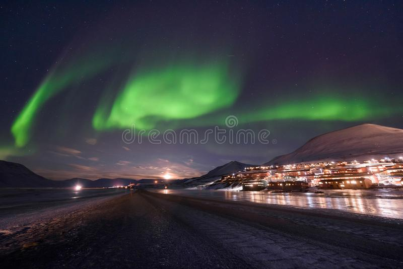 Polar arctic Northern lights aurora borealis sky star in Norway Svalbard in Longyearbyen city travel mountains royalty free stock photography