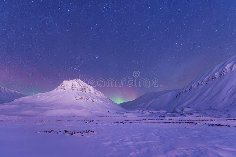 Polar arctic Northern lights aurora borealis sky star in Norway Svalbard in Longyearbyen the moon mountains. The polar arctic Northern lights aurora borealis sky stock photo