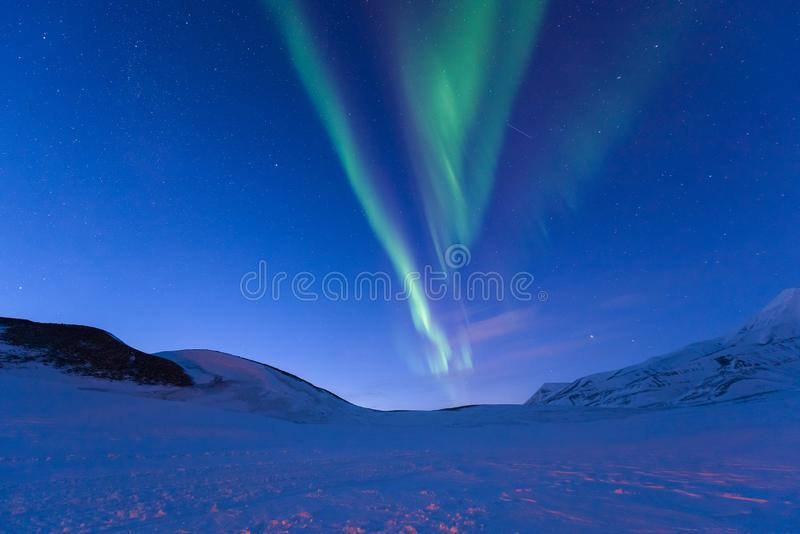 Polar arctic Northern lights aurora borealis sky star in Norway Svalbard in Longyearbyen the moon mountains stock images