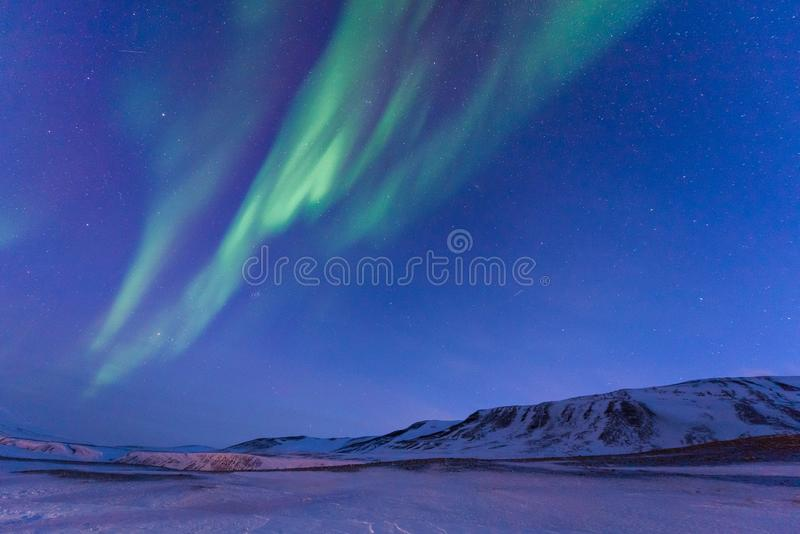 Polar arctic Northern lights aurora borealis sky star in Norway Svalbard in Longyearbyen the moon mountains. The polar arctic Northern lights aurora borealis sky stock photo