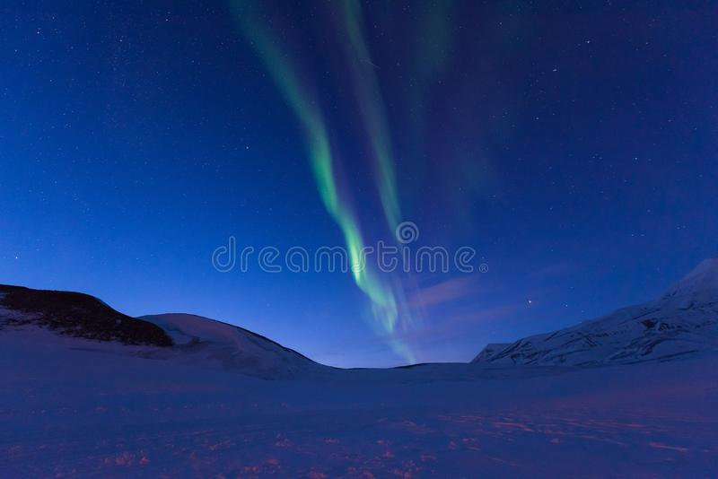 Polar arctic Northern lights aurora borealis sky star in Norway Svalbard in Longyearbyen the moon mountains royalty free stock images