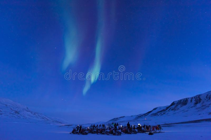Polar arctic Northern lights aurora snowscooter borealis sky star in Norway Svalbard in Longyearbyen the moon mountains royalty free stock photography