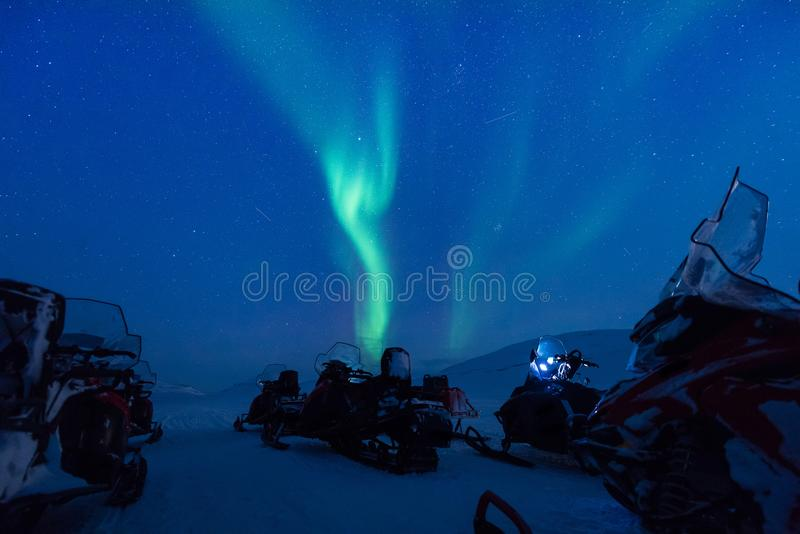 Polar arctic Northern lights aurora snowscooter borealis sky star in Norway Svalbard in Longyearbyen the moon mountains. The polar arctic Northern lights aurora stock photo