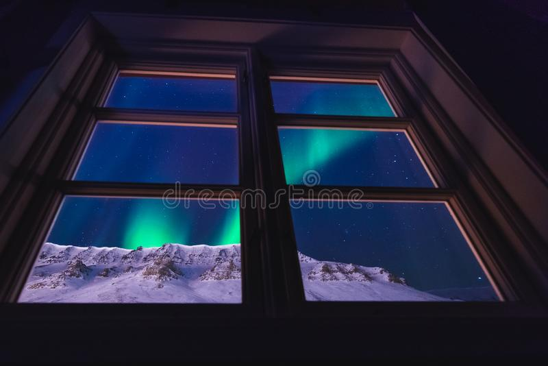 Polar arctic Northern lights aurora snowscooter borealis sky star in Norway Svalbard in Longyearbyen the moon mountains royalty free stock photos