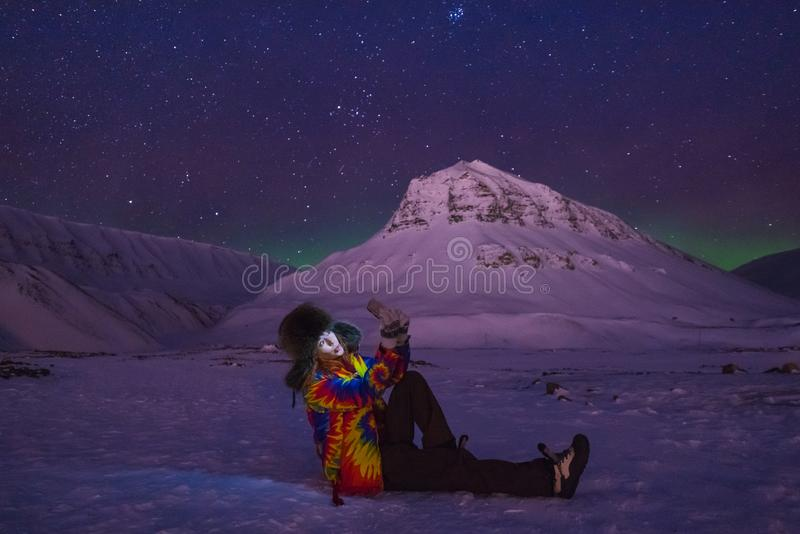 Arctic Northern lights aurora borealis sky star in Norway travel blogger girl man Svalbard in Longyearbyen city the moon mountains stock images