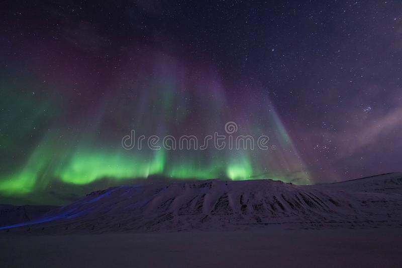 Arctic Northern lights aurora borealis sky star in Norway travel Svalbard in Longyearbyen city the moon mountains. The polar arctic Northern lights aurora stock images