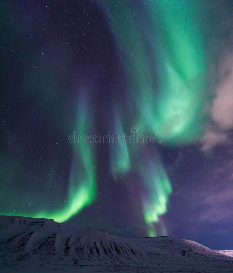 Arctic Northern lights aurora borealis sky star in Norway travel Svalbard in Longyearbyen city the moon mountains. The polar arctic Northern lights aurora royalty free stock photos