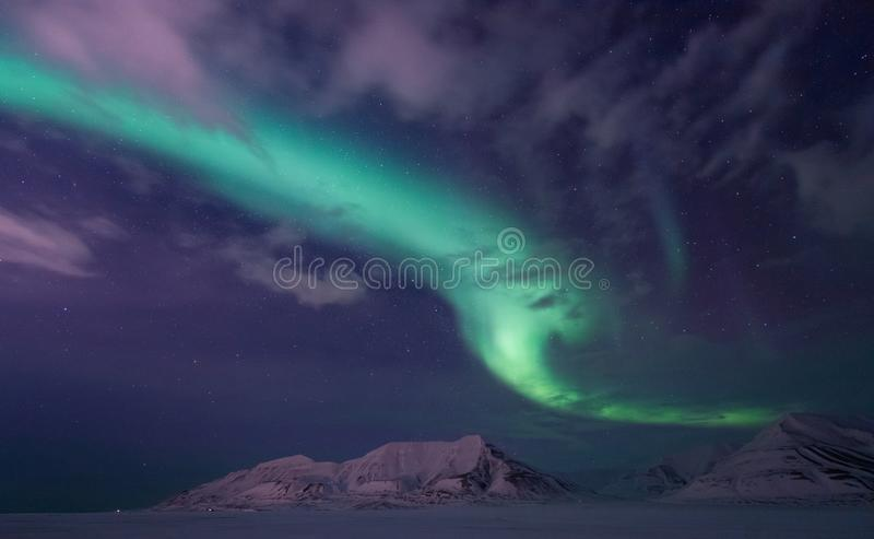 Arctic Northern lights aurora borealis sky star in Norway travel Svalbard in Longyearbyen city the moon mountains. The polar arctic Northern lights aurora stock photo