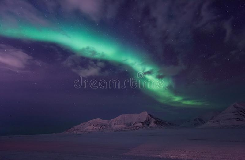 Arctic Northern lights aurora borealis sky star in Norway travel Svalbard in Longyearbyen city the moon mountains. The polar arctic Northern lights aurora royalty free stock image