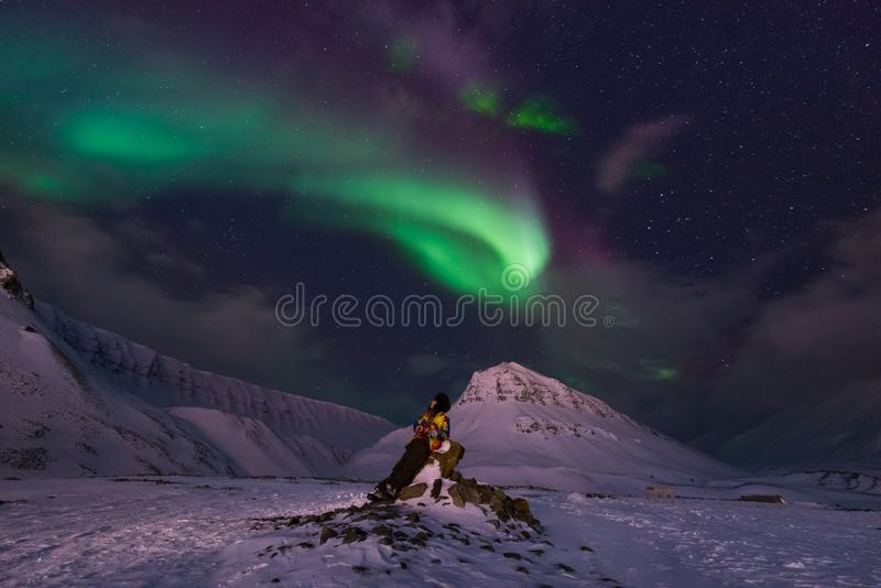 Arctic Northern lights aurora borealis sky star in Norway travel Svalbard in Longyearbyen city the moon mountains royalty free stock photography