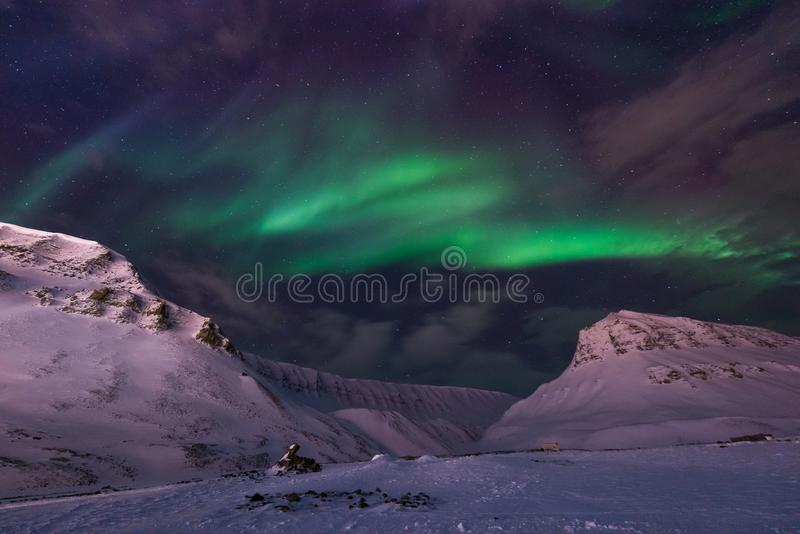 Arctic Northern lights aurora borealis sky star in Norway travel Svalbard in Longyearbyen city the moon mountains. The polar arctic Northern lights aurora royalty free stock photo