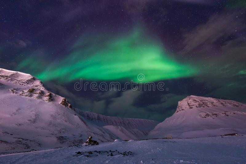Arctic Northern lights aurora borealis sky star in Norway travel Svalbard in Longyearbyen city the moon mountains. The polar arctic Northern lights aurora stock photography