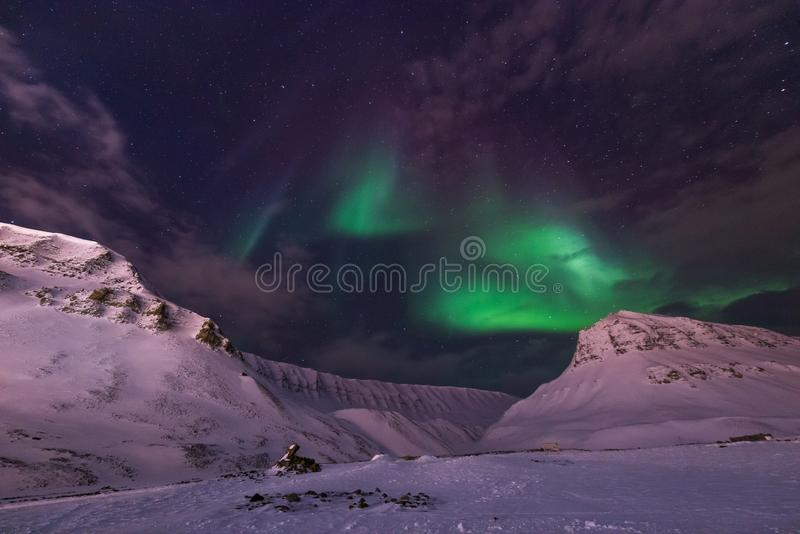 Arctic Northern lights aurora borealis sky star in Norway travel Svalbard in Longyearbyen city the moon mountains royalty free stock images