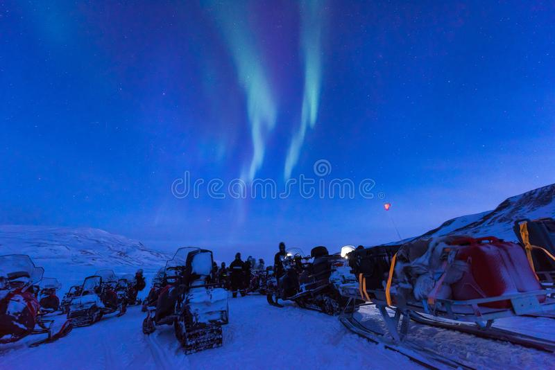 Polar arctic Northern lights aurora snowscooter borealis sky star in Norway Svalbard in Longyearbyen the moon mountains stock photos