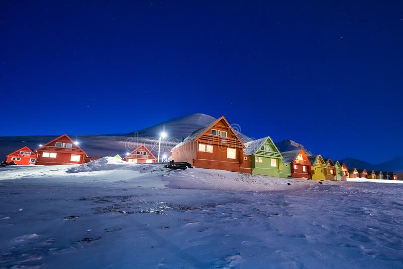 Polar arctic Northern lights aurora snowscooter borealis sky star in Norway Svalbard in Longyearbyen the moon mountains stock photography