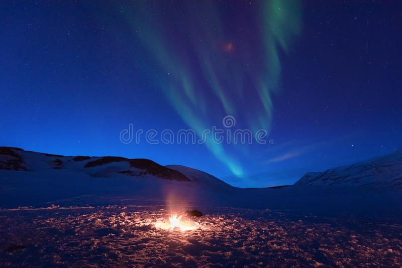 Polar arctic Northern lights aurora snowscooter borealis sky star in Norway Svalbard in Longyearbyen the moon mountains. The polar arctic Northern lights aurora stock photography