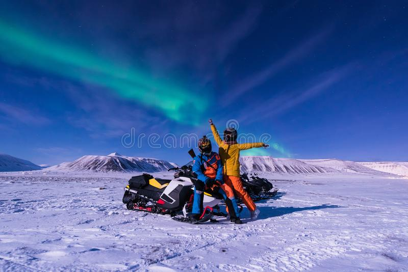 The polar arctic snowmobile Northern lights aurora borealis sky star in Norway Svalbard in Longyearbyen city man mountains stock images