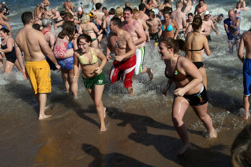 Olar bear plunge with people in swim suits jumping into ice cold sea water