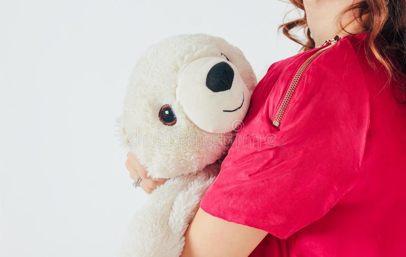 Polar bear toy on hands of young woman in bright pink dress. On gray background , concept of Valentine`s day royalty free stock photos