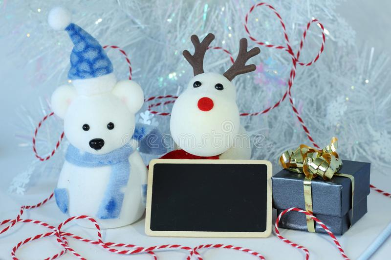 Polar bear wearing a hat and a blue scarf for Christmas party decoration with a empty message slate royalty free stock image