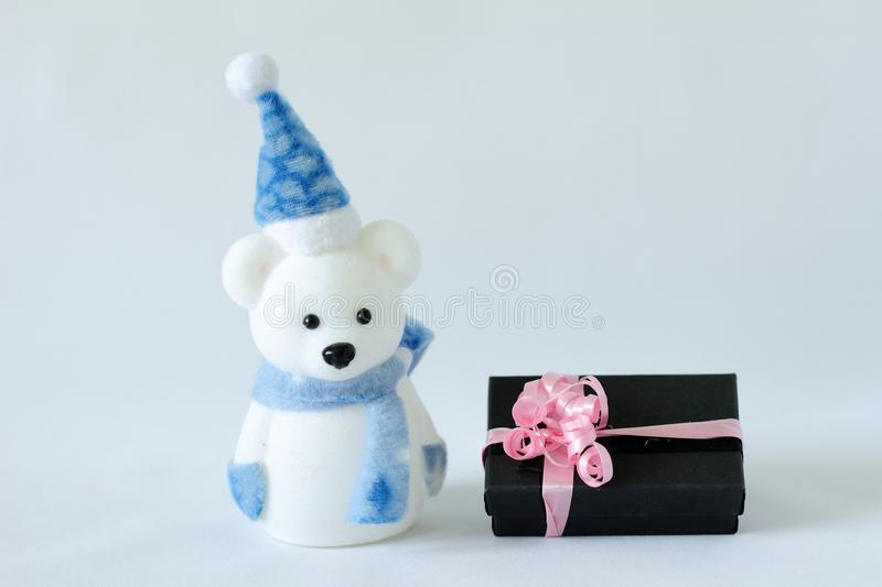 Polar bear wearing a hat and a blue scarf posed next to gifts with shiny knots on a Christmas holiday decor. A polar bear wearing a hat and a blue scarf posed stock photography