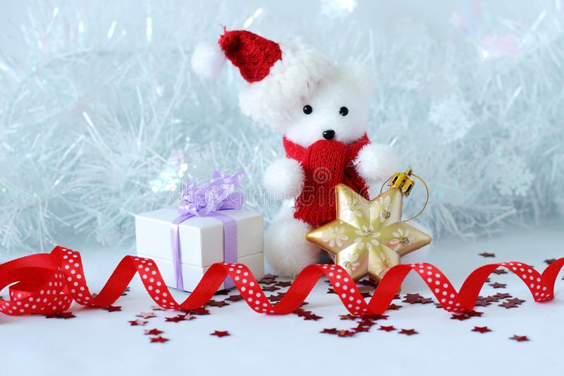 Polar bear wearing a hat and a blue scarf posed next to gifts with shiny knots on a Christmas holiday decor. A polar bear wearing a hat and a blue scarf posed stock images
