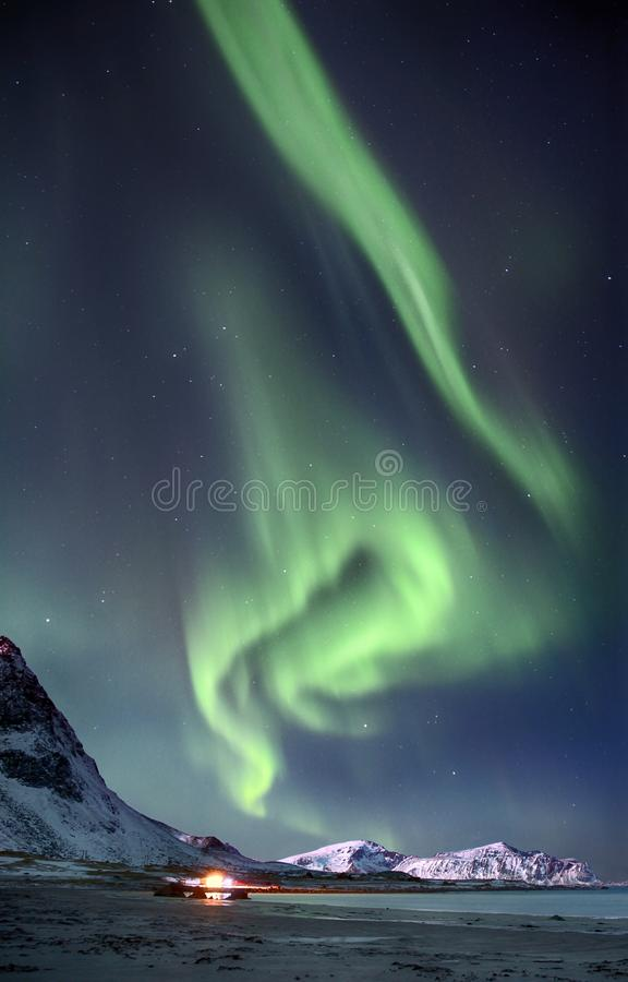 Polar lights in the sky above the mountains on the northern beach in Norway. Polar lights in the sky above the mountains on the northern beach of Lofoten islands royalty free stock images