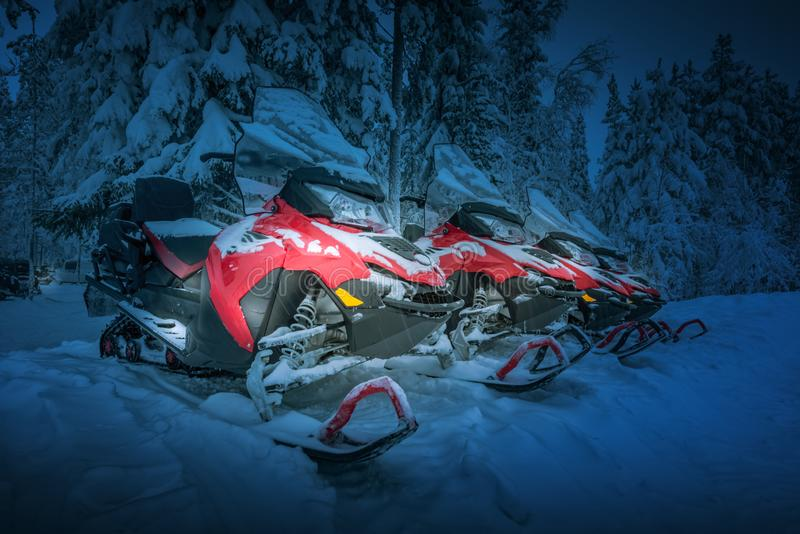 Polar night landscape with row of red snowmobiles. Polar night in Lapland, Finland. Red snowmobiles are ready for adventure ride. Vehicles parked in line near stock photos