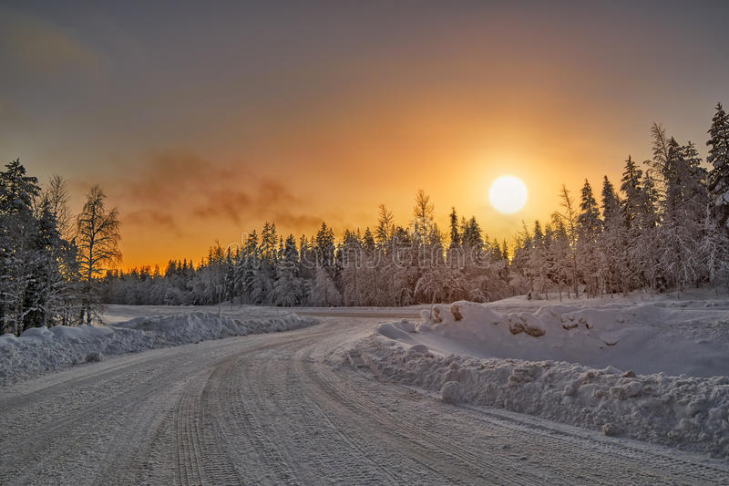 Polar Night Sunset over road in Finland. Bright Colorful Winter Polar Night Sunset over road in Lapland, Finland royalty free stock photo