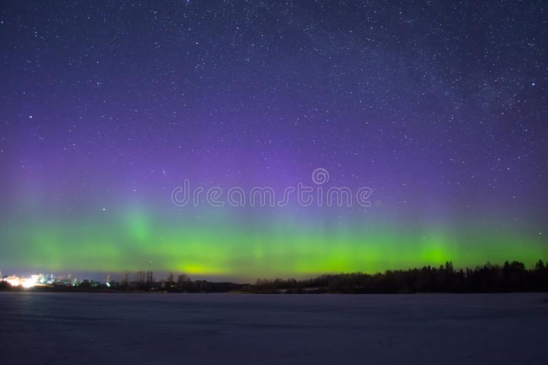 Polar northen lights aurora borealis at night in the starry sky above the lake with the island and the silhouette trees by the for. Polar northen lights aurora stock photo