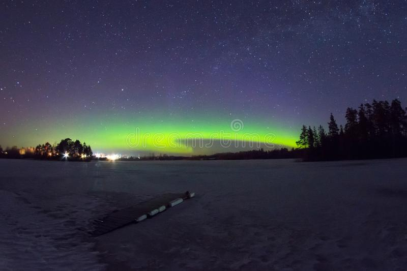 Polar northen lights aurora borealis at night in the starry sky above the lake with the island and the silhouette of the trees by. The forest. Glowing arc over royalty free stock photography