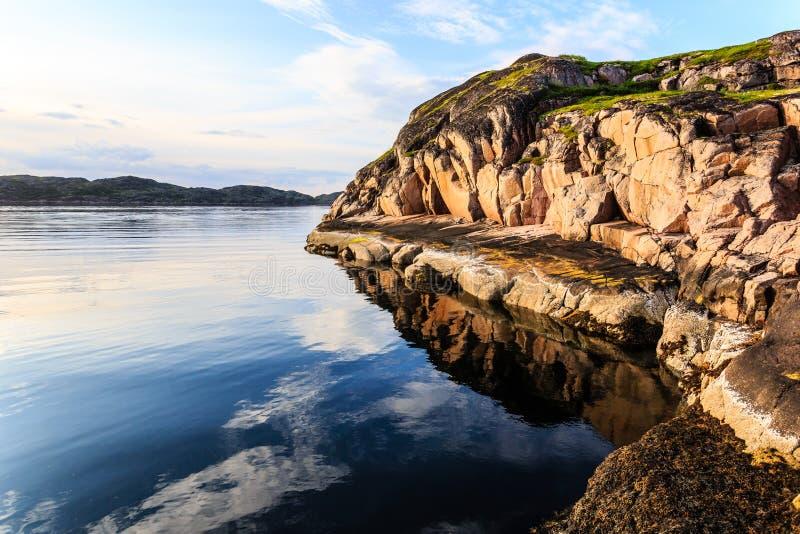 Polarer Nordsommer Schöne Küstenlinie von Barents-Meer, Felsen, die in der ruhigen Wasseroberfläche sich reflektieren Ansicht des stockbild