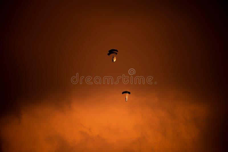 POLARISATION internationale de salon de l'aéronautique de Bucarest, silhouette de parachute avec des étincelles sur le ciel de co photographie stock