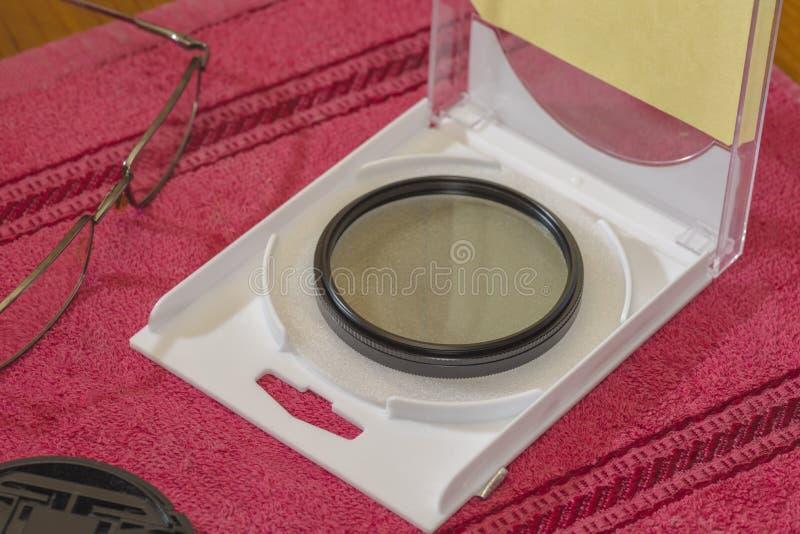 Polariserande FÄRDIGT filter för linsen på tabellen i en öppen ask arkivfoto