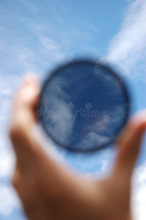Polarizer. Circular Polarizing Filter in action, deepens the blue sky. (focus is on the clouds through Polarizer royalty free stock images
